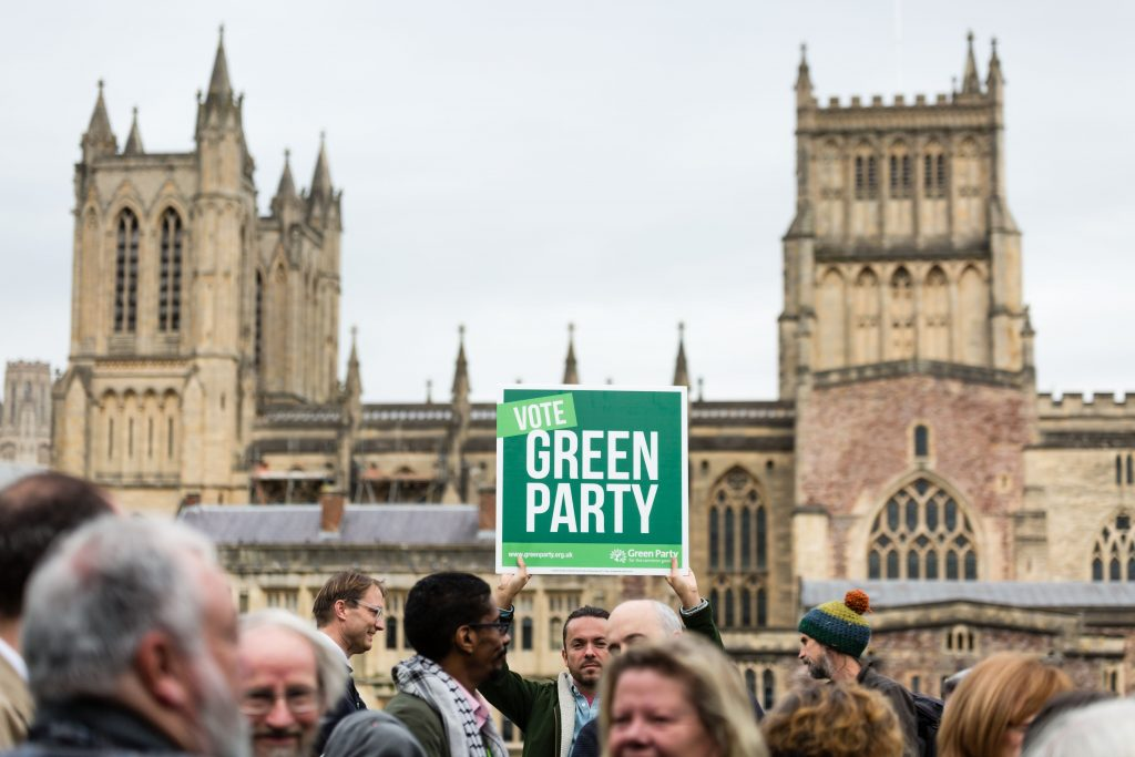 A man holding a 'Vote Green' sign in Bristol