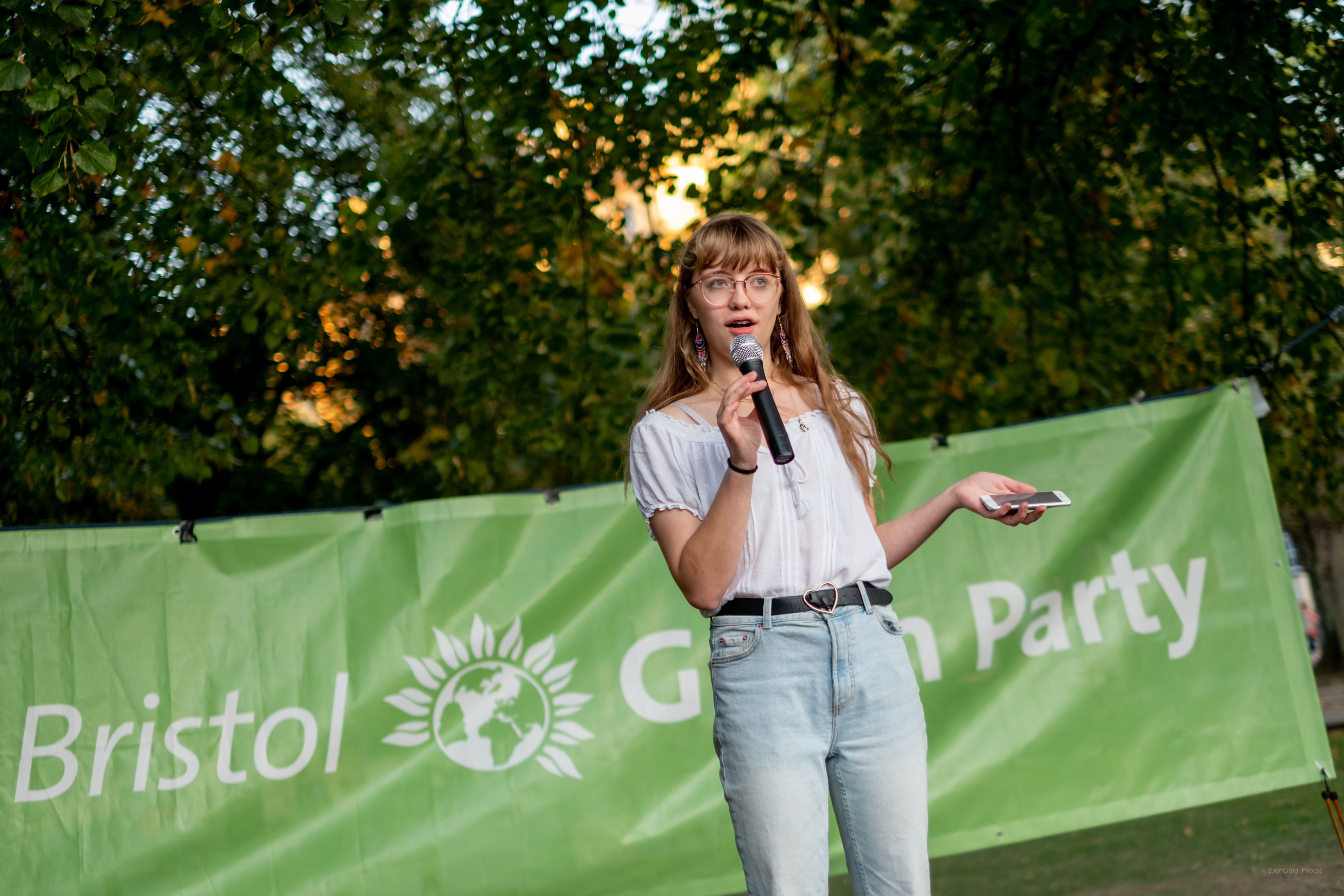 A photo of Lily Fitzgibbon talking on a microphone in front of a Green Party banner