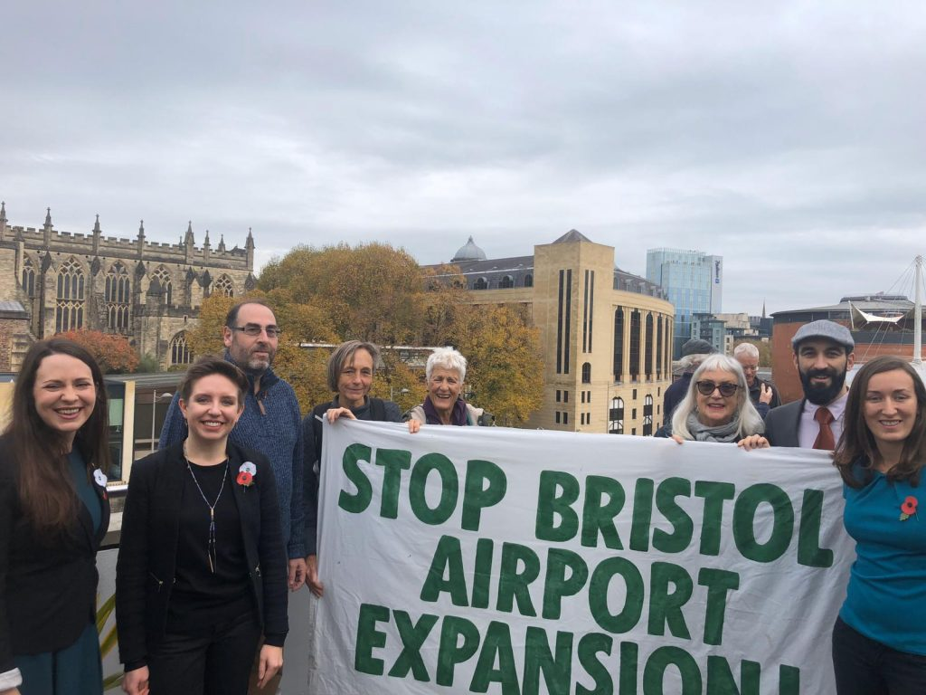 Green councillors and members on a roof holding a stop bristol expansion banner